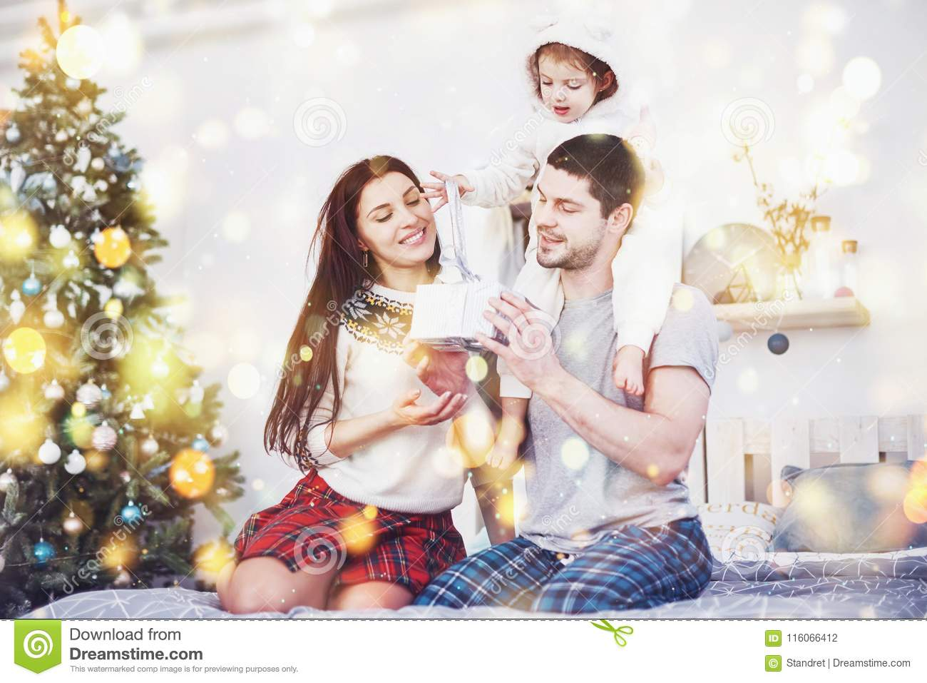 Happy family at christmas in morning opening gifts together near the fir tree. The concept of family happiness and well