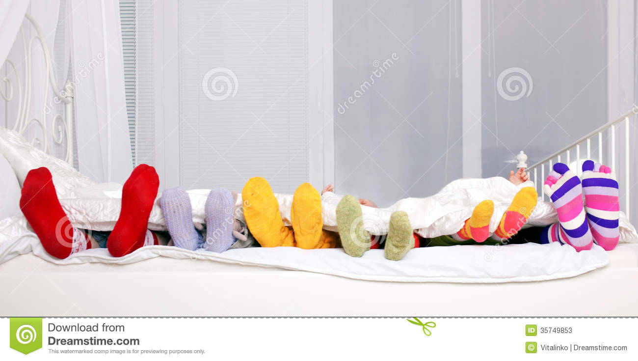 happy family in colorful socks on white bed stock photos image 35749853. Black Bedroom Furniture Sets. Home Design Ideas