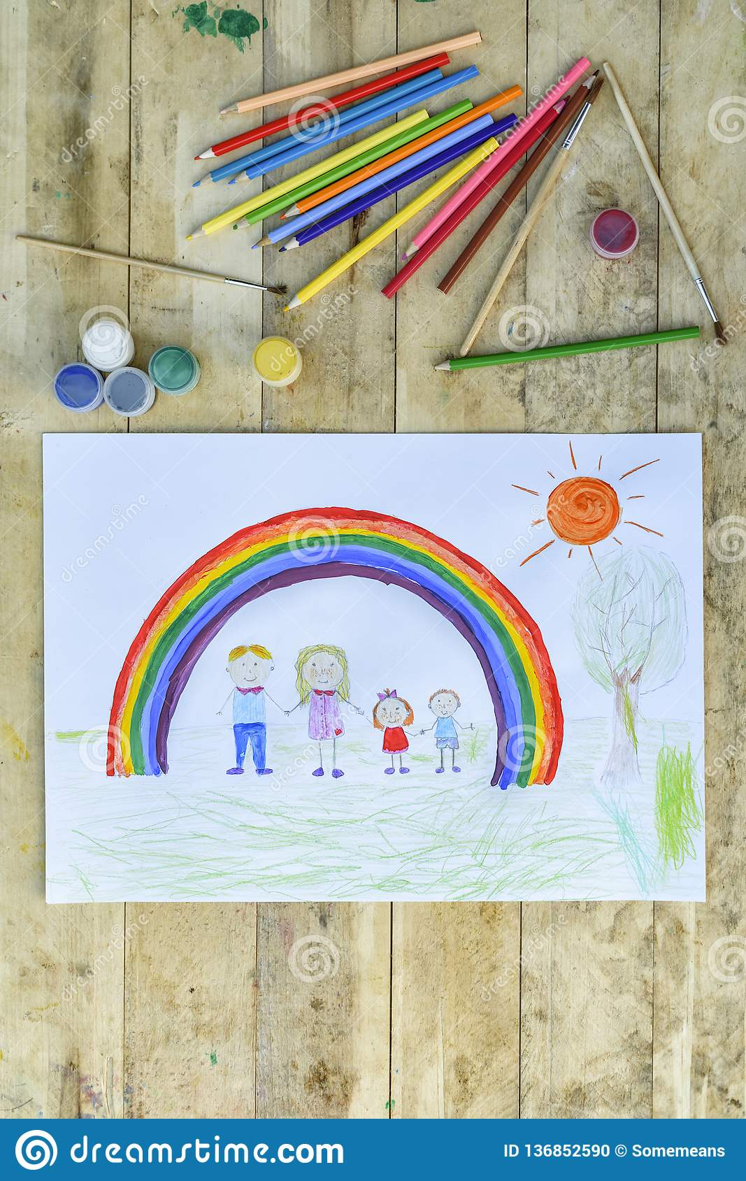 Happy family concept. Sheet with a pattern on a wooden table: parents and children hold hands against background of rainbow and