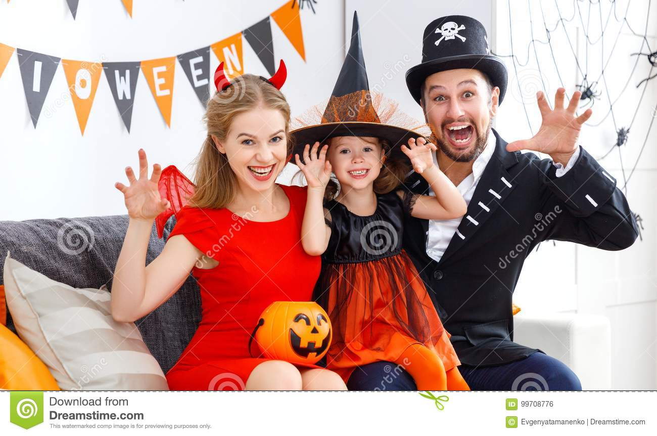 Happy family in costumes getting ready for halloween