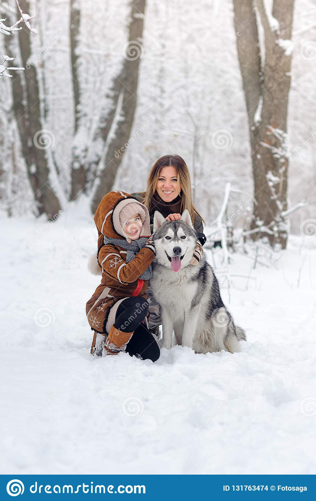 The happy family with dogs huskies poses in beautiful for the snow wood. Trees in snow