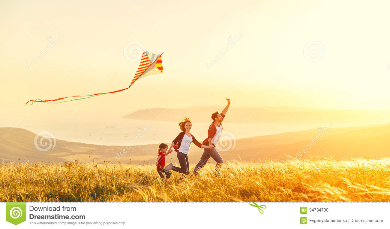 Happy family father of mother and child daughter launch a kite o