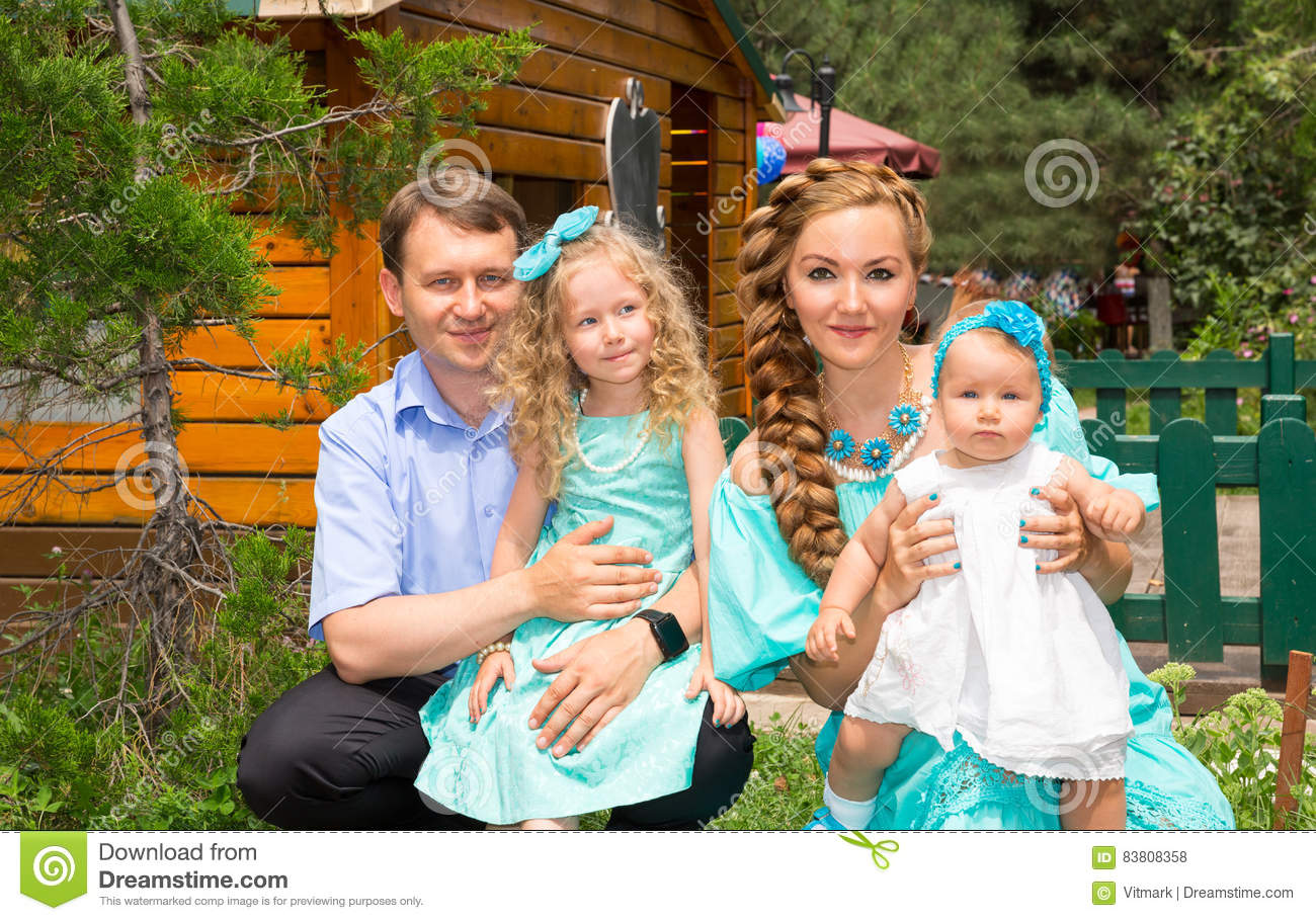 Happy family of father, mother and two children in outdoor on a summer day. Portrait parents and kids on nature. Positive human em