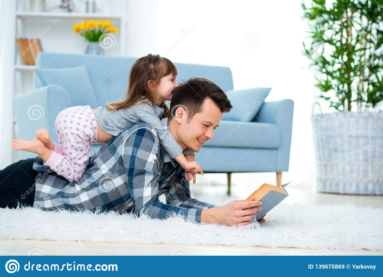 Happy family and father`s day concept. Dad with daughter spending time togetherness at home. Cute little girl on dad`s back lyin