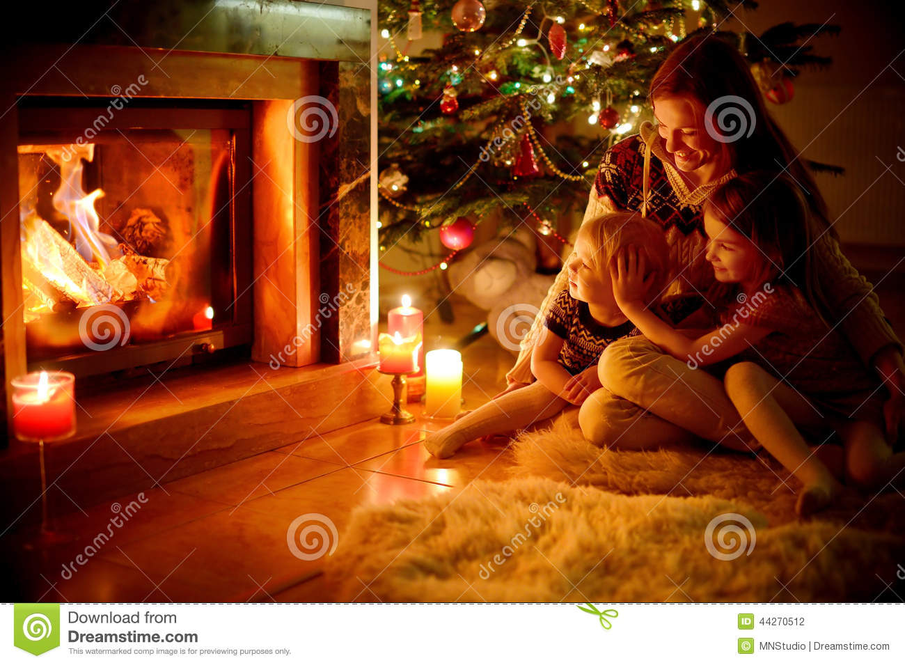 happy family by a fireplace on christmas stock photo