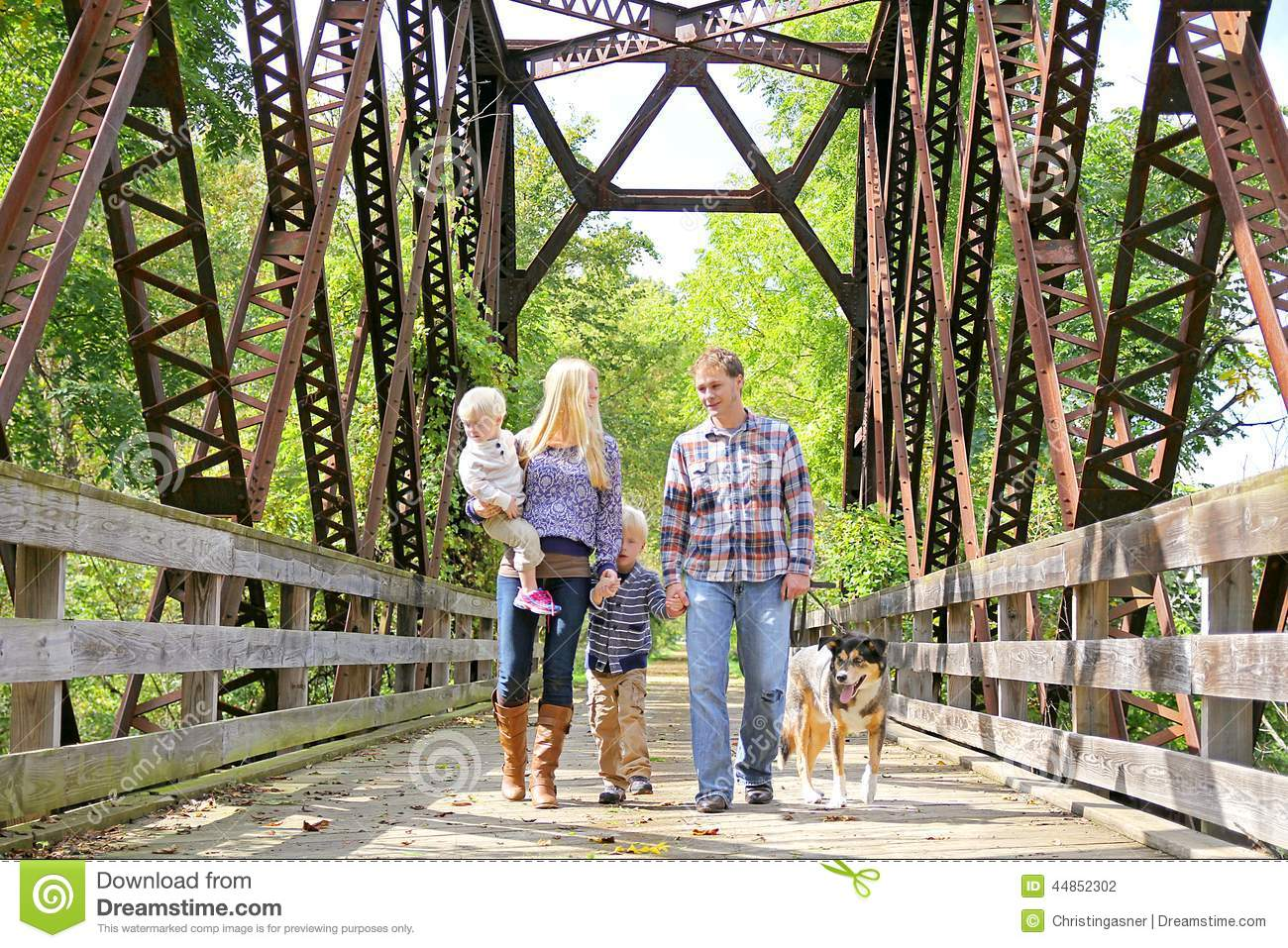 happy-family-four-people-walking-dog-outside-bridge-including-mother-father-young-child-toddler-brother-across-44852302.jpg
