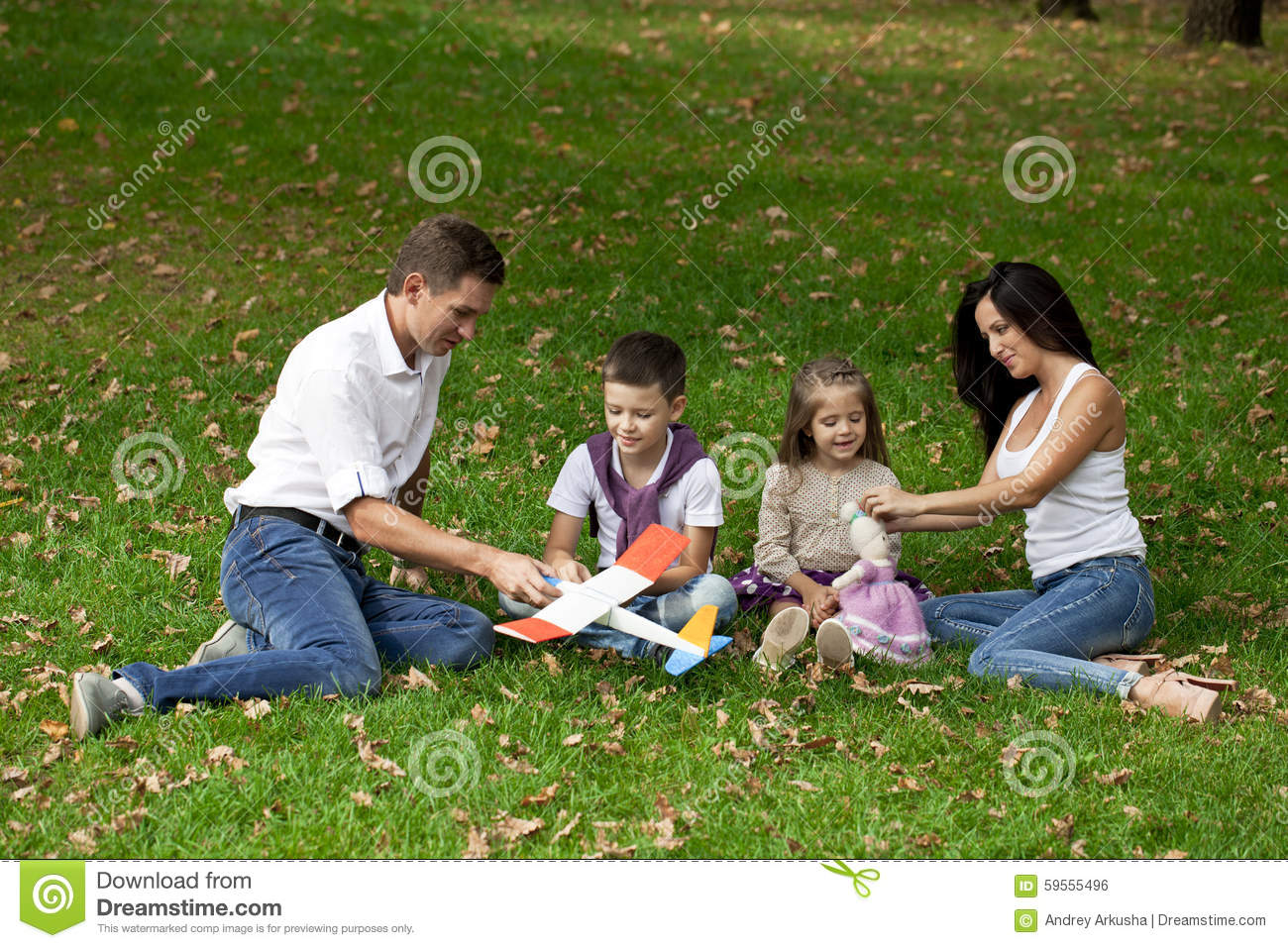Happy family of four, resting in the autumn park