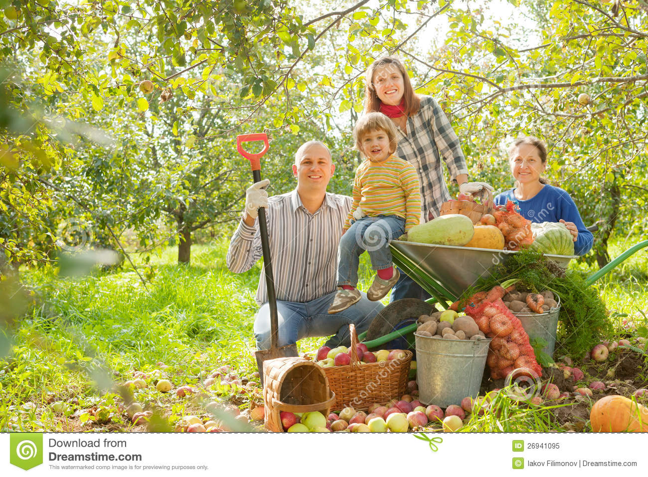 Happy Family With Harvest In Garden Royalty Free Stock