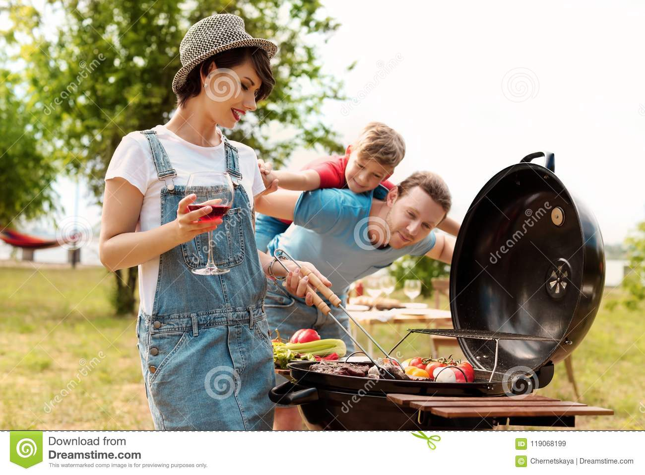 Happy family having barbecue with modern grill