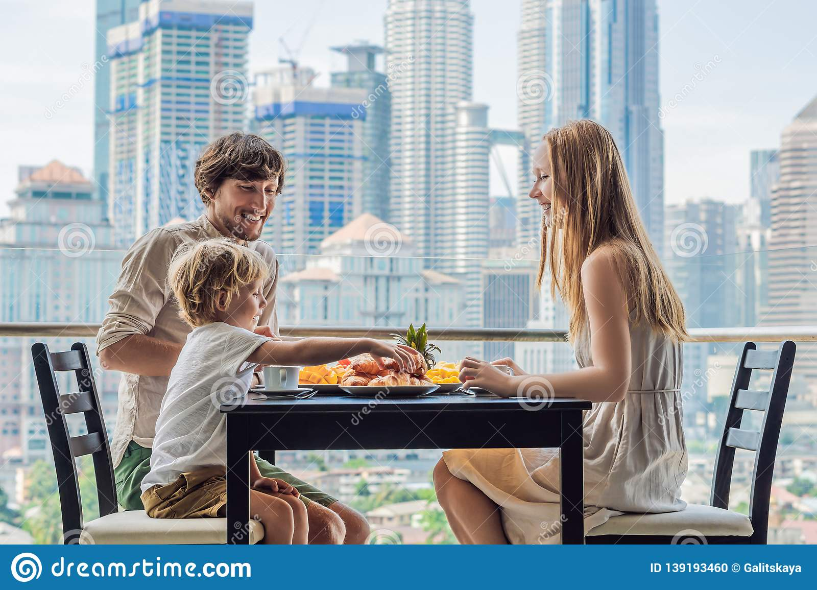 Happy family having breakfast on the balcony. Breakfast table with coffee fruit and bread croisant on a balcony against