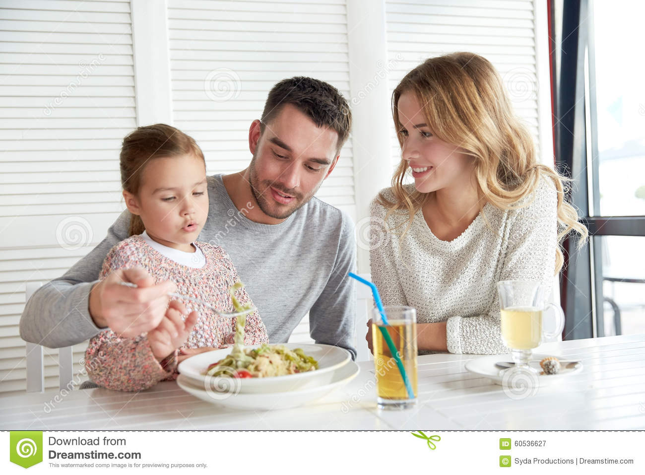 Happy family having dinner at restaurant or cafe