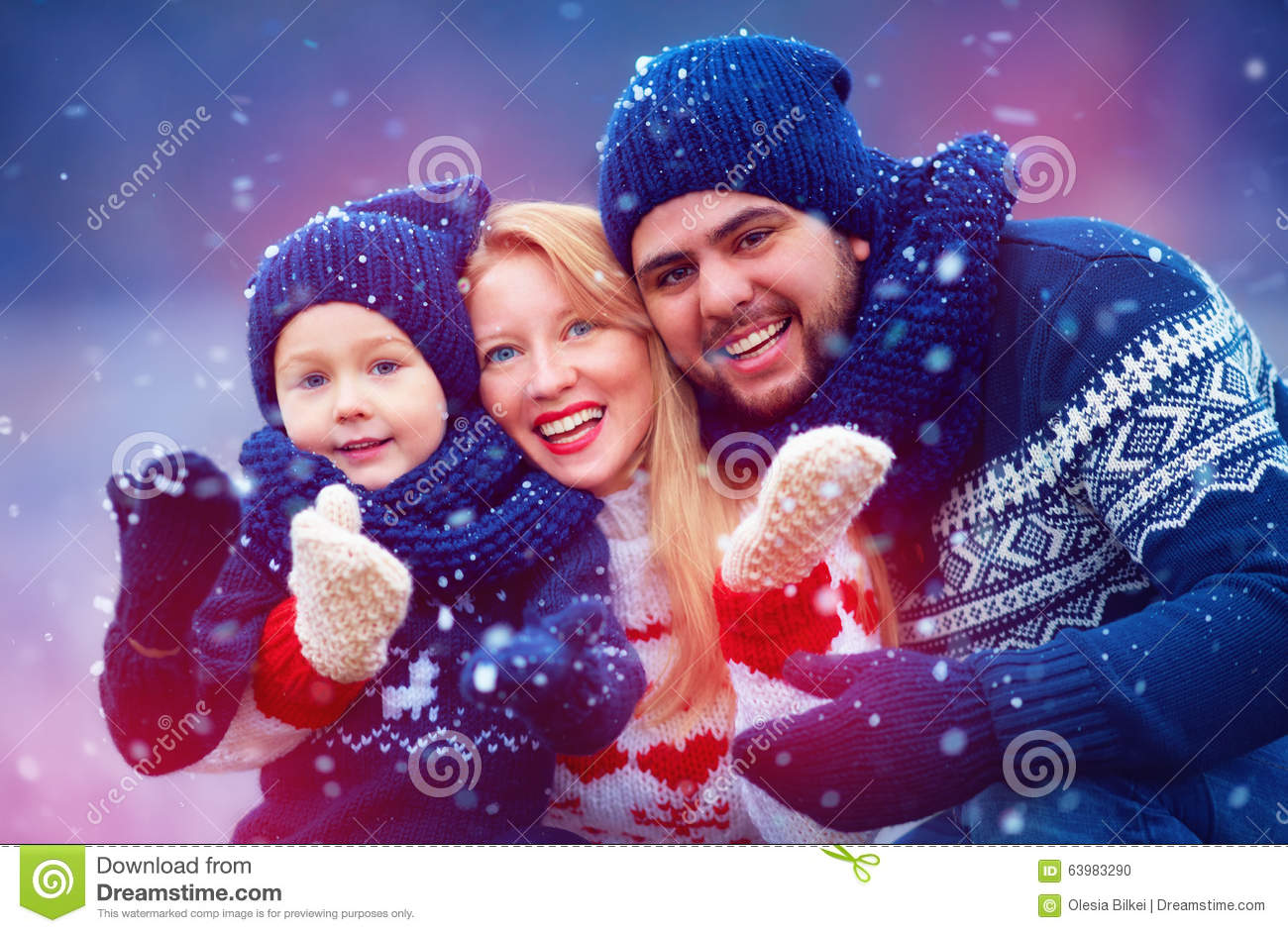 Happy family having fun under snow during winter holidays
