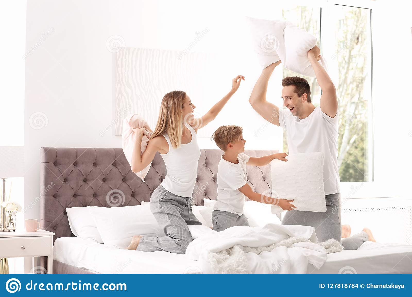 Happy family having pillow fight on bed