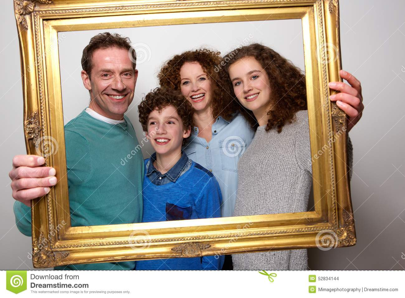 happy family holding picture frame and smiling stock photo image 52834144. Black Bedroom Furniture Sets. Home Design Ideas