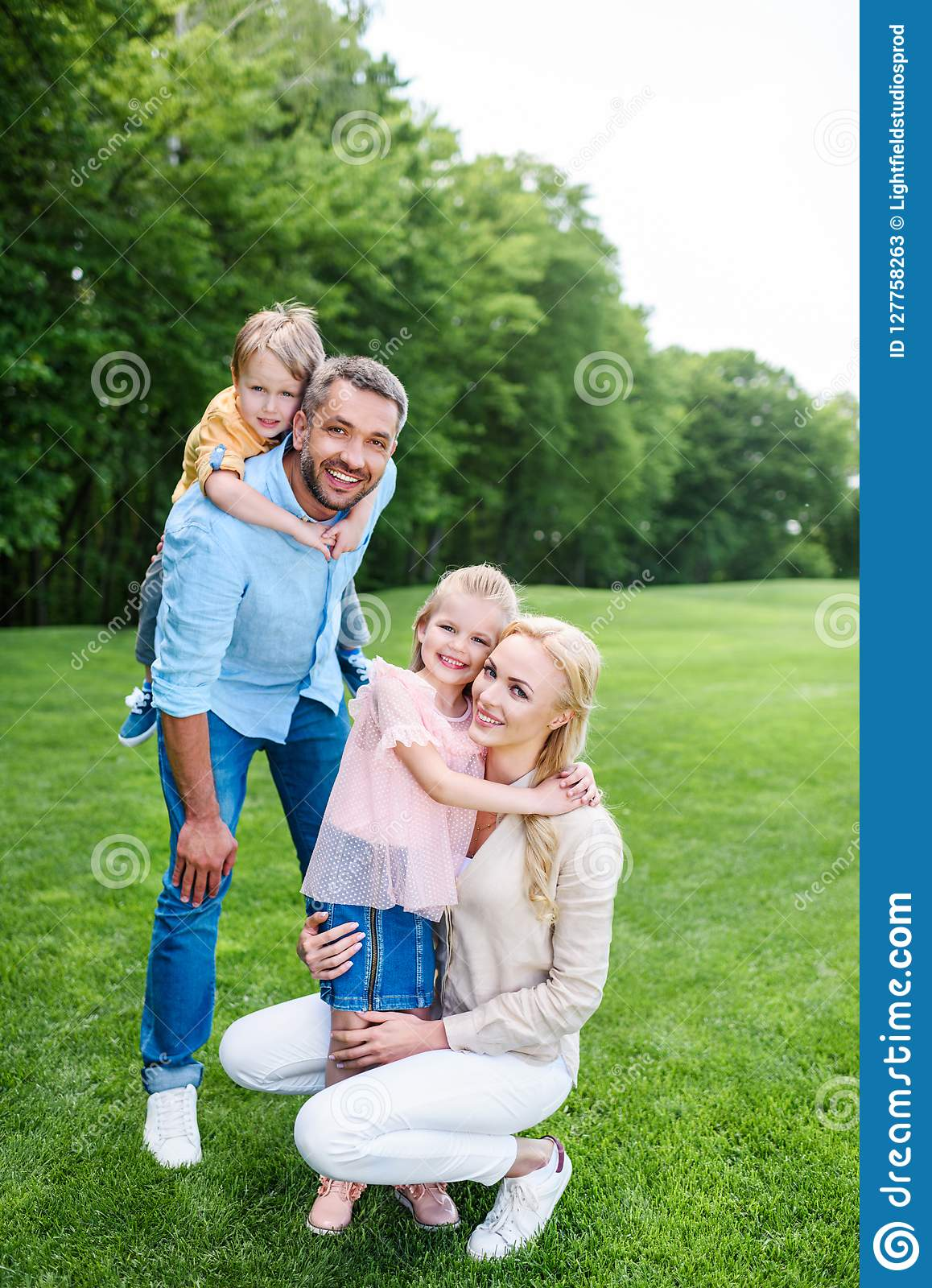 happy family hugging and smiling at camera while spending time together