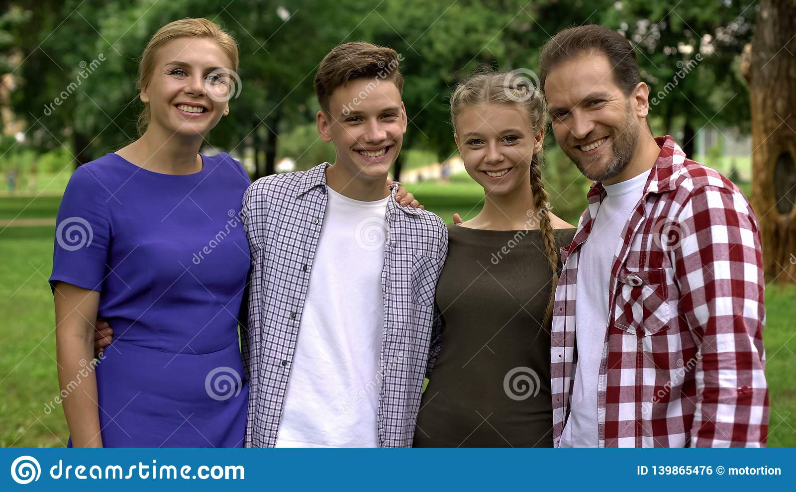Happy family hugging and smiling in park, posing into camera, pride for children
