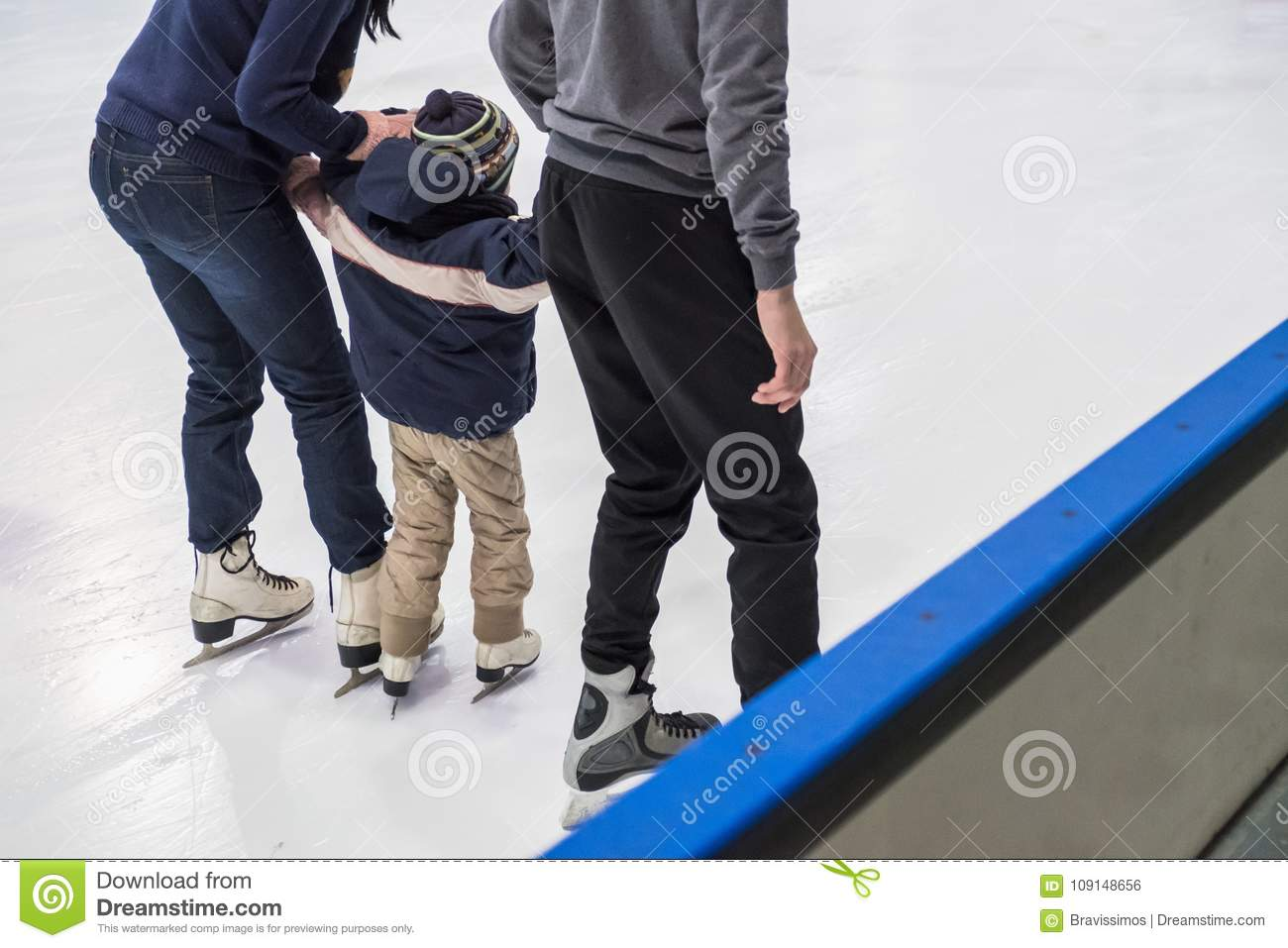 Happy family indoor ice skating at rink. Winter