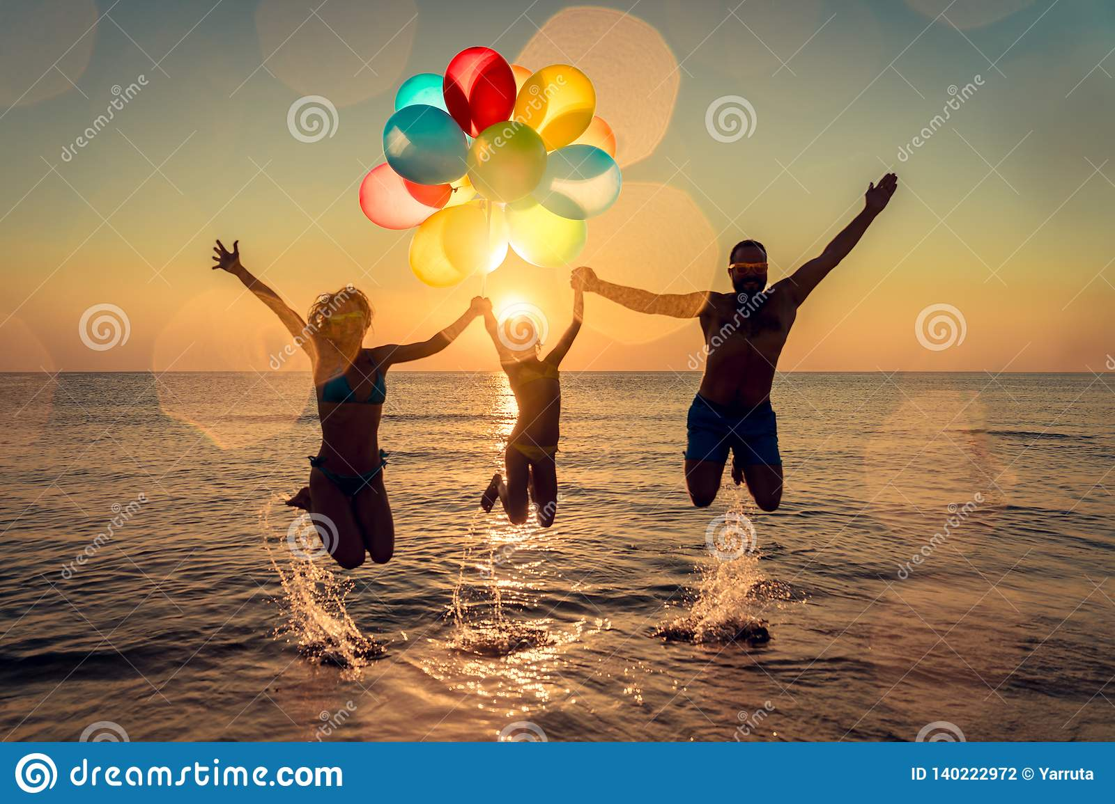 Happy family jumping in the sea