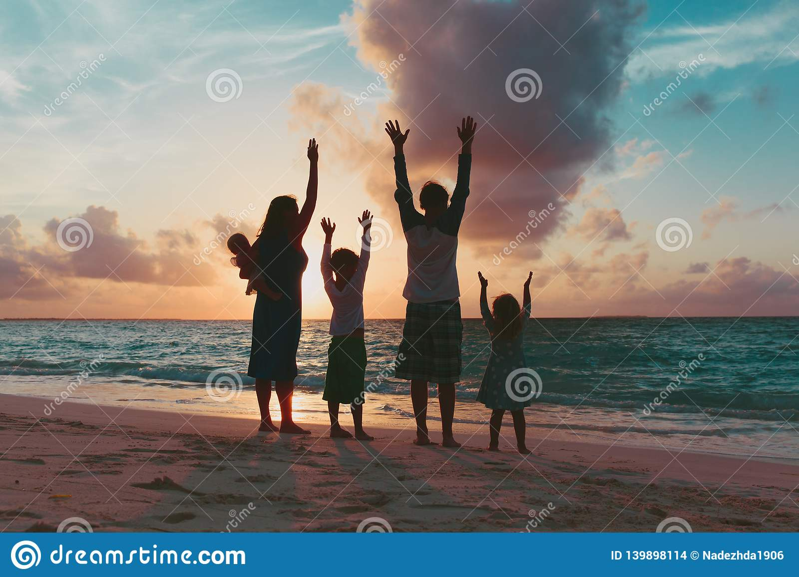 Happy family with kids having fun at sunset beach