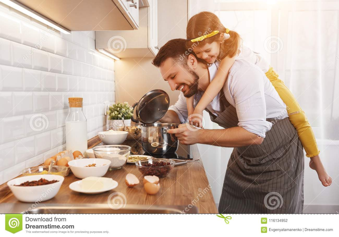 Happy family in kitchen. Father and child daughter knead dough a