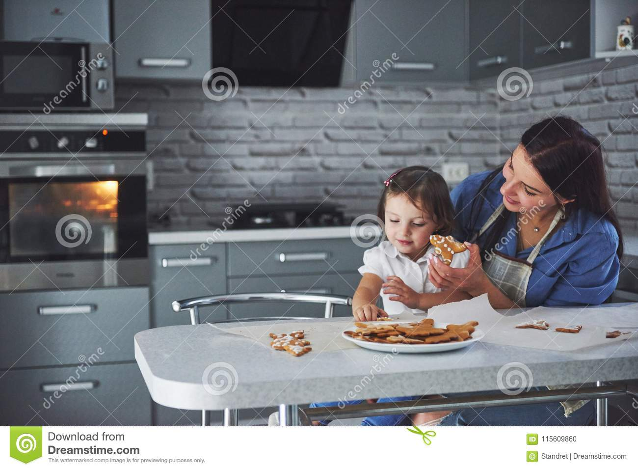 Happy family in the kitchen. Holiday food concept. Mother and daughter decorate cookies. Happy family in making homemade