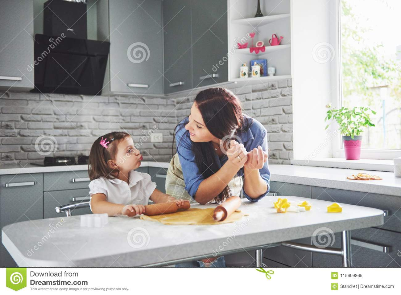 Happy family in the kitchen. Holiday food concept. Mother and daughter preparing the dough, bake cookies. Happy family