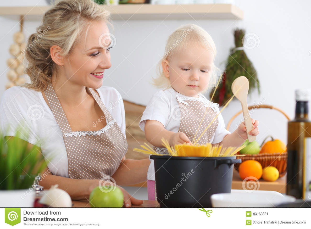 Happy family in kitchen - Happy Family In The Kitchen Mother And Child Daughter Cooking Pasta Stock Photo