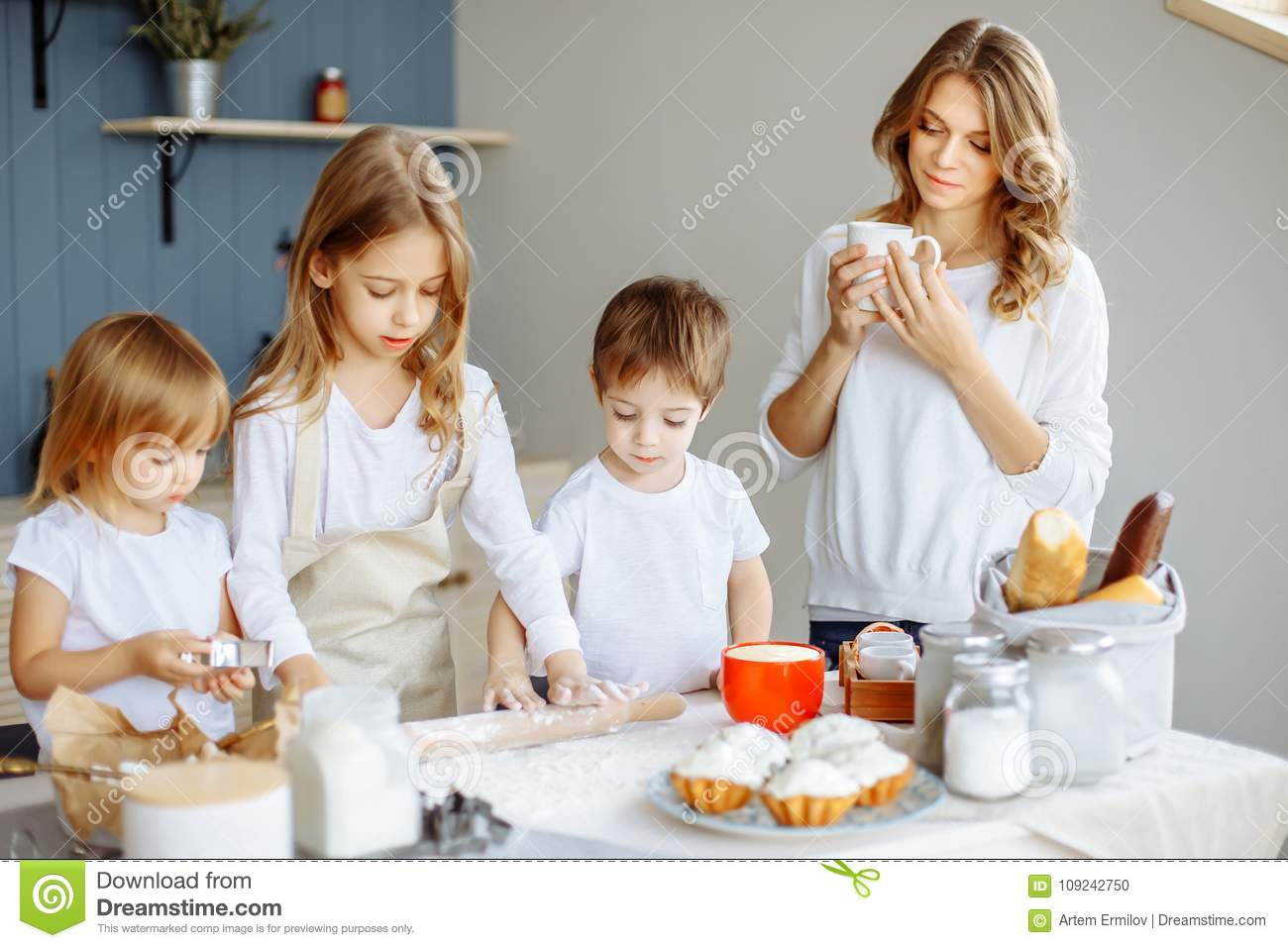 Happy family in the kitchen. Mother and her cute kids are cooking cookies