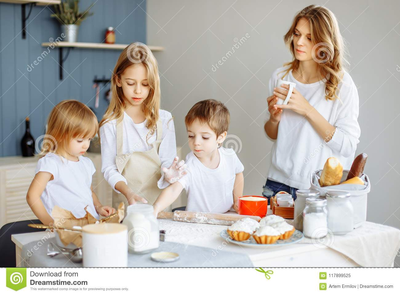 Happy family in the kitchen. Mother and her cute kids are cooking cookies.