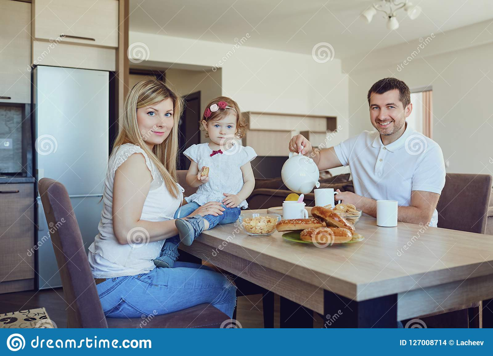 A happy family in the kitchen while sitting at a table.