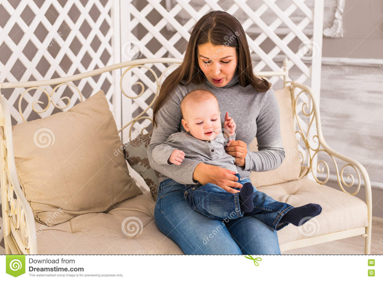 Happy family laughing faces, mother holding adorable child baby boy, smiling and hugging, healthy kid joyful mom