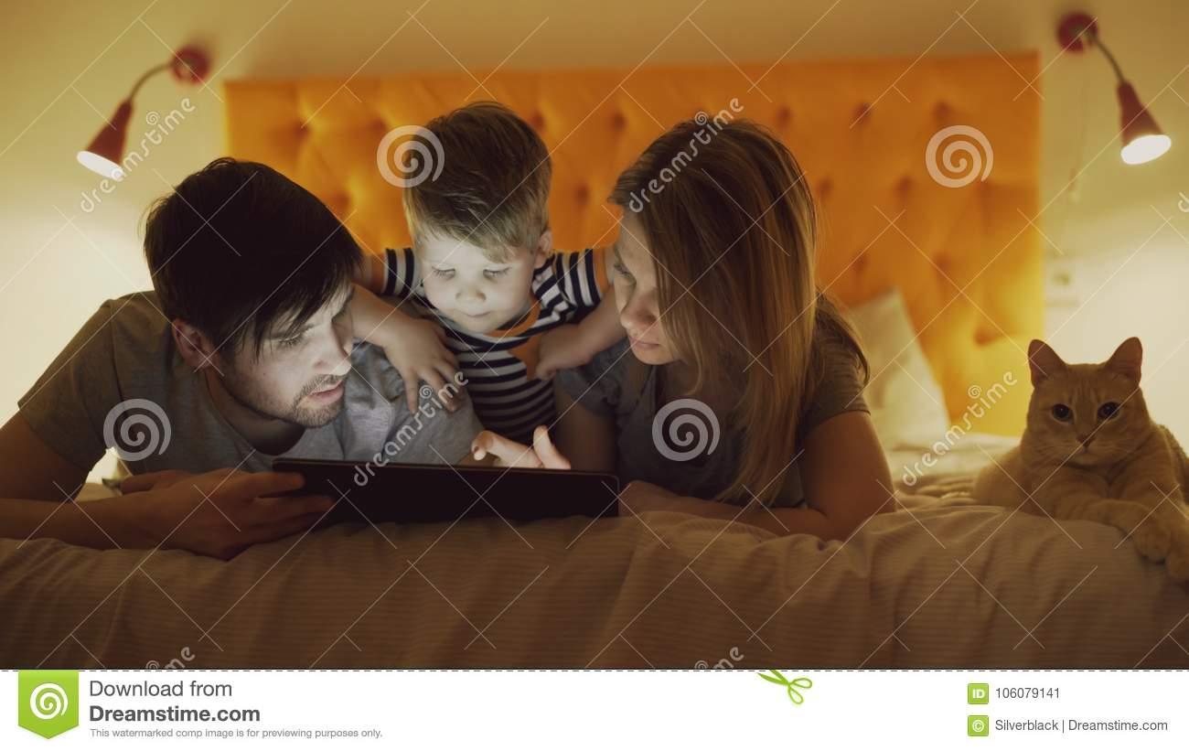 Happy family with little son and funny cat lying in bed at home and using tablet computer for playing game before