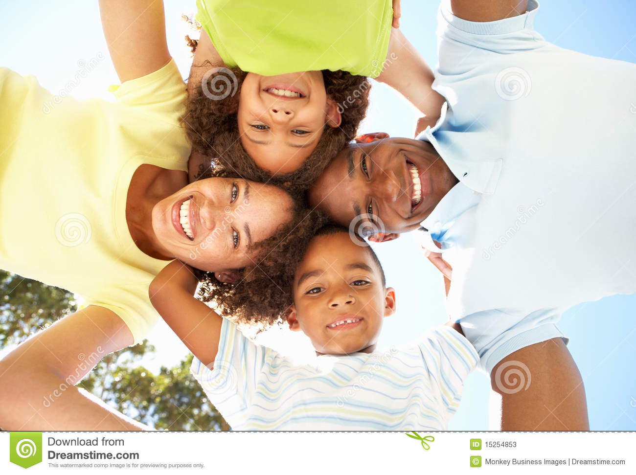 Happy Family Looking Down Into Camera In Park