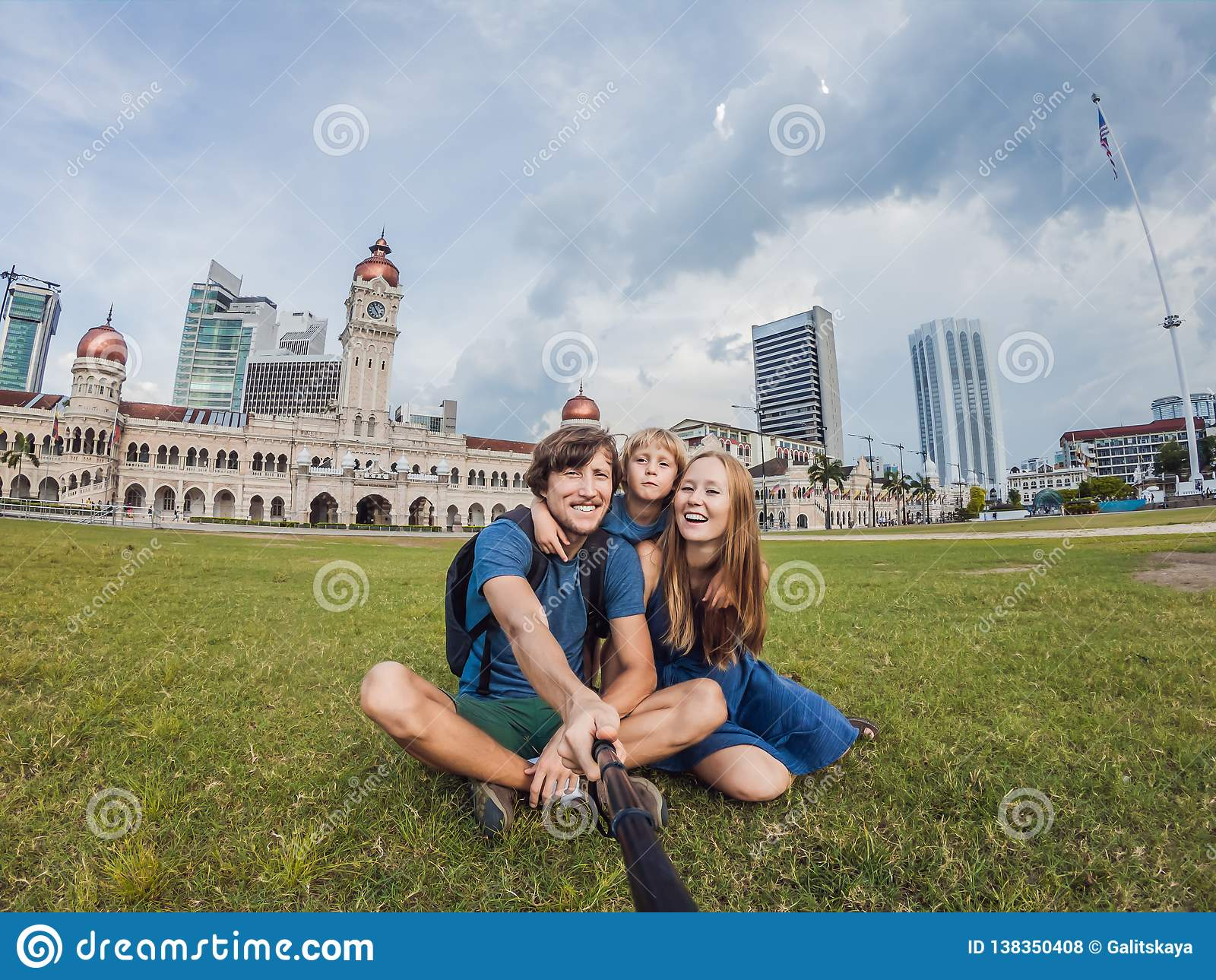 Happy family makes selfie on the background on background of Merdeka square and Sultan Abdul Samad Building. Traveling