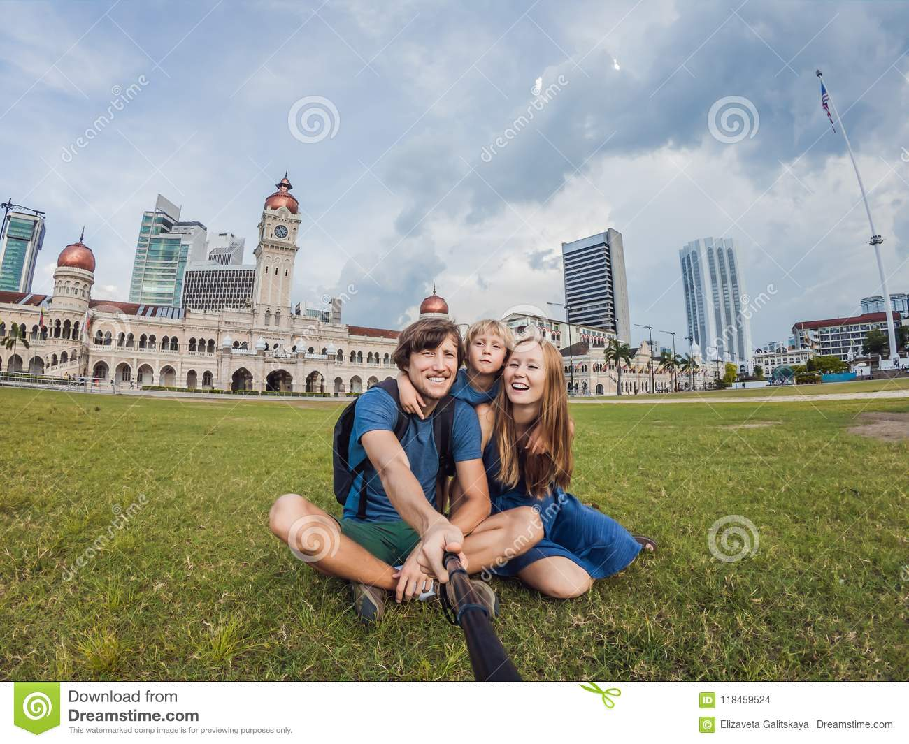 happy family makes selfie on the background on background of Merdeka square and Sultan Abdul Samad Building. Traveling with child