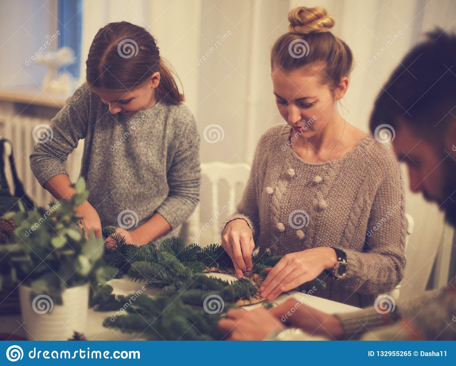 Happy family making an advent wreath with the daughter