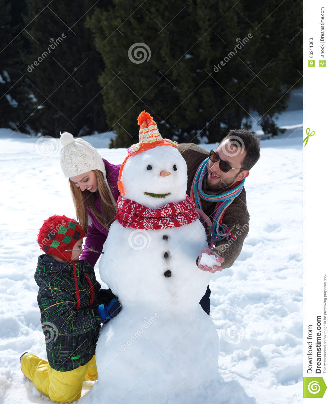 Young Happy Beautiful Family Playing Together On The Beach: Happy Family Making Snowman Stock Photo