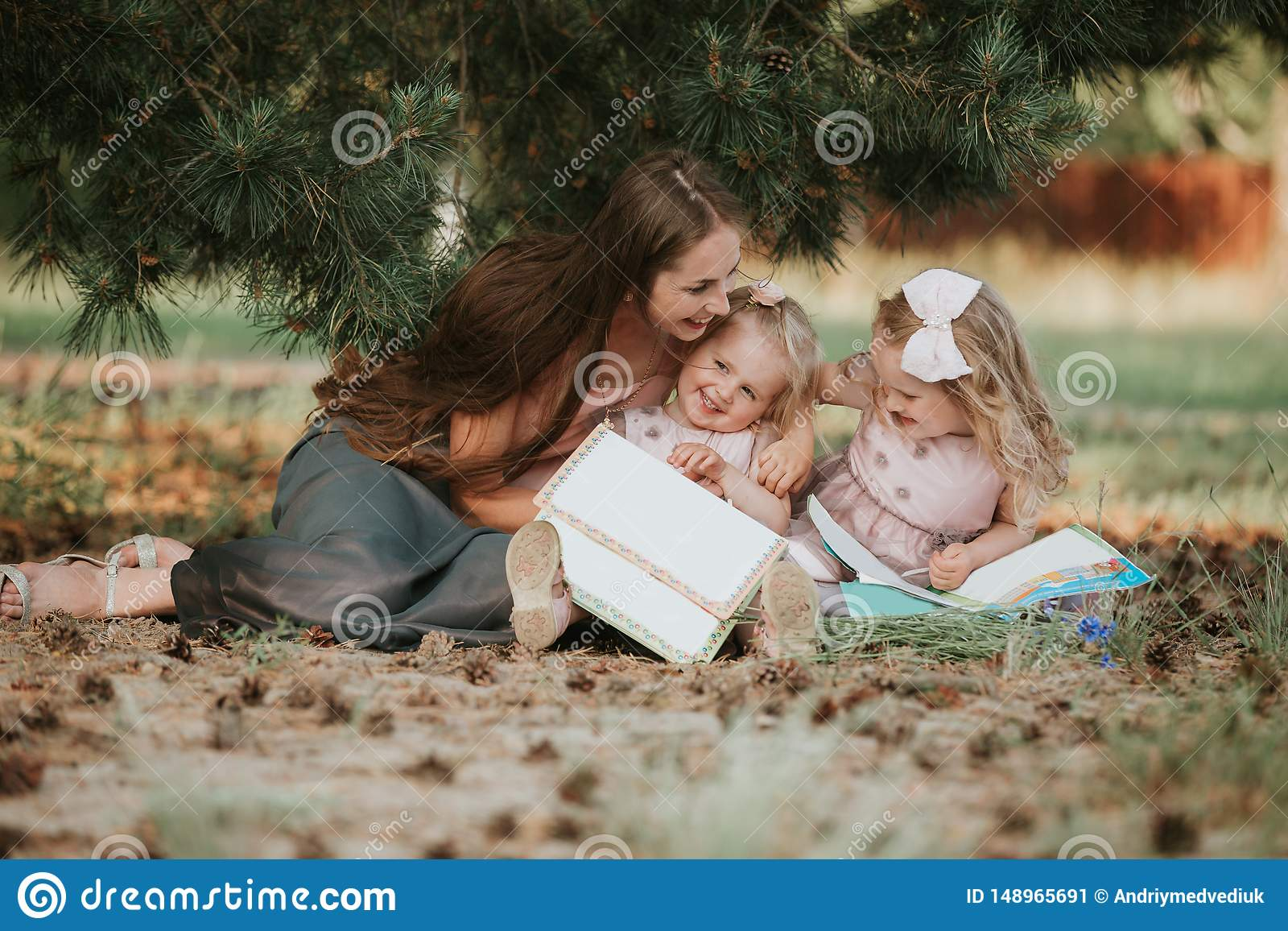 Happy family - mom and two daughters are sitting in a meadow and reading a book. Picnic