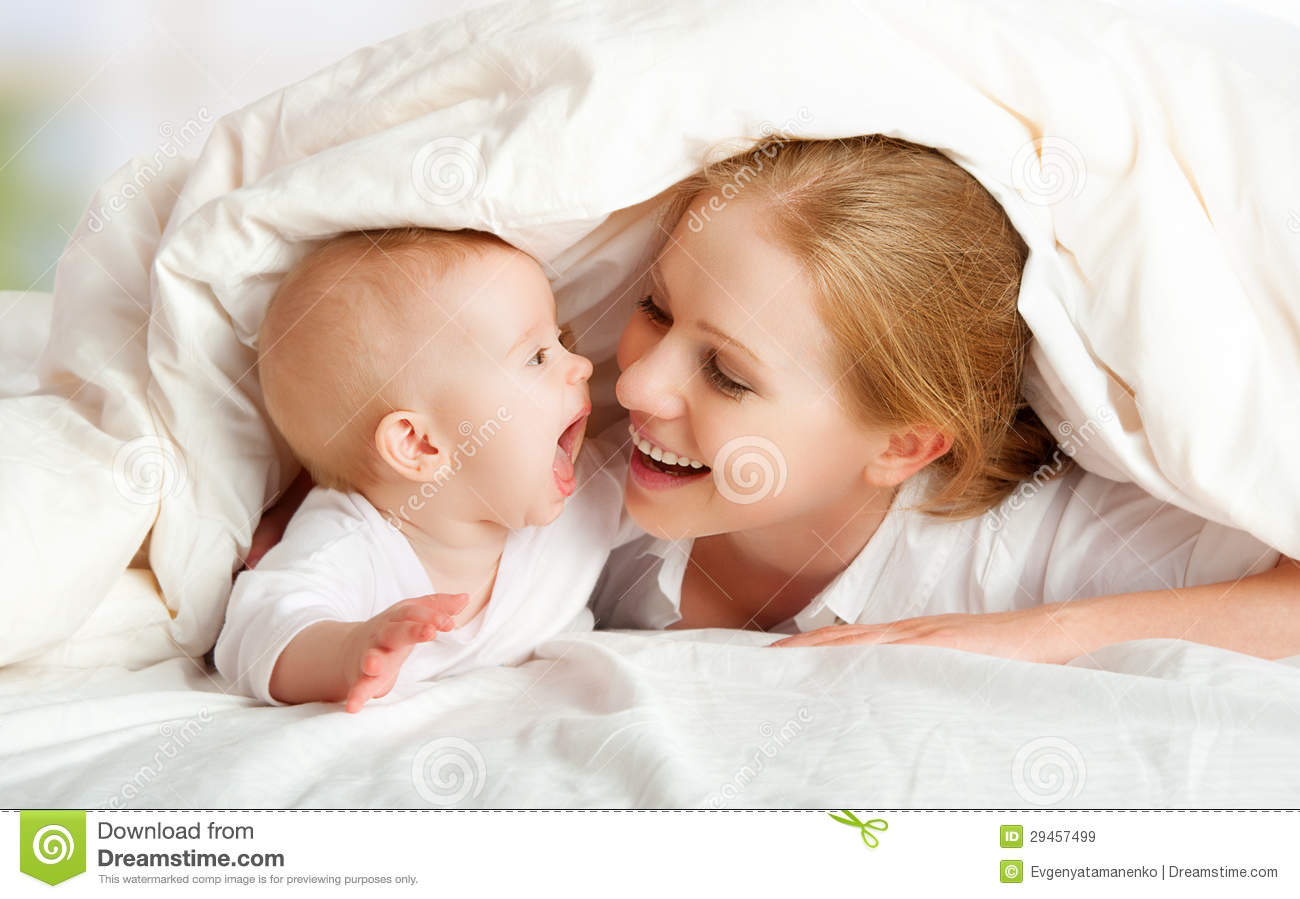 Mother and baby playing under blanket happy family mother and baby