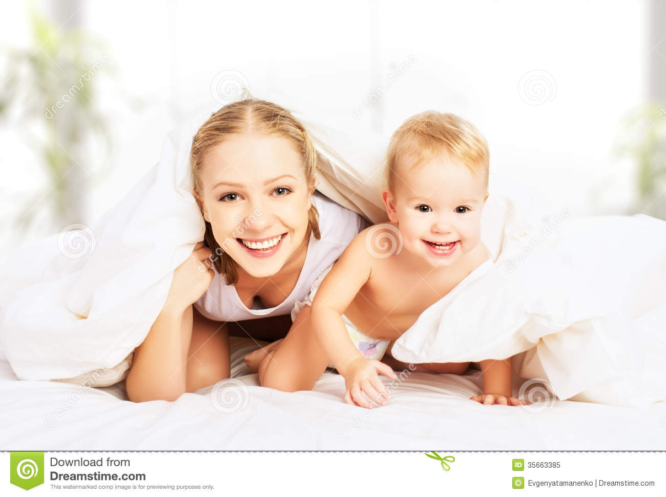 Happy family mother and baby under blankets in bed