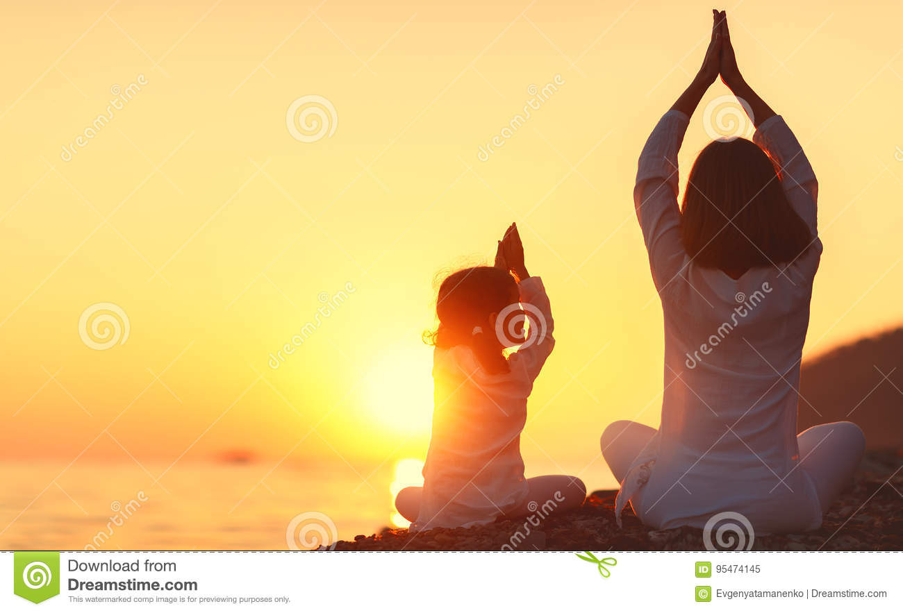 Happy family mother and child doing yoga, meditate in lotus position on beach
