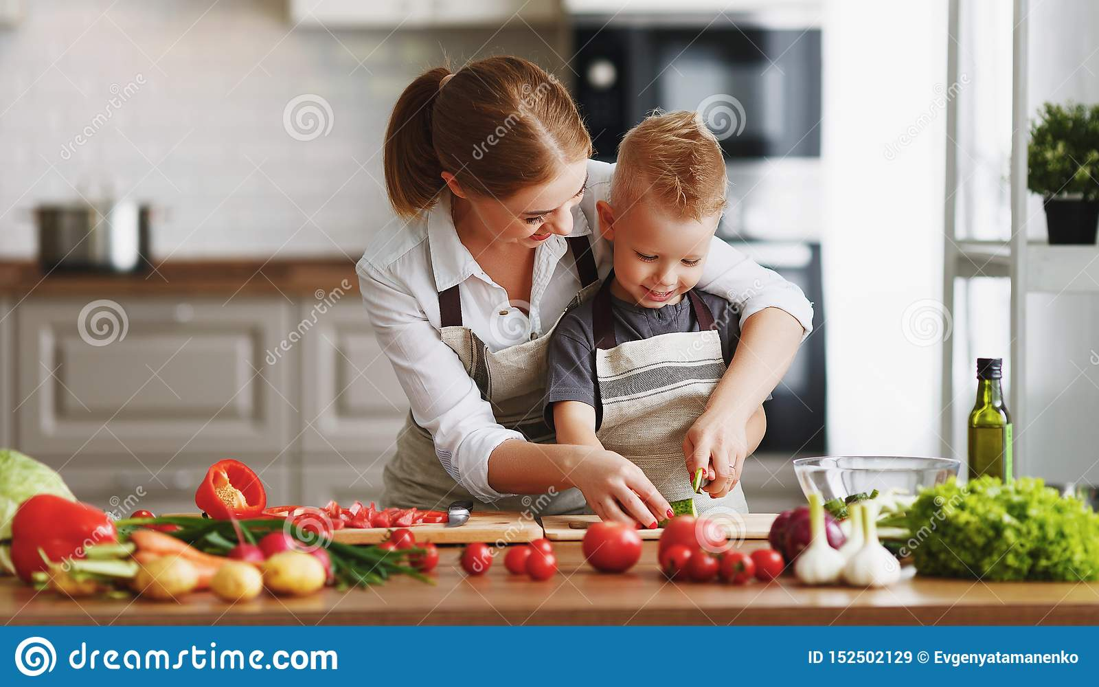 Happy family mother with child son preparing vegetable salad