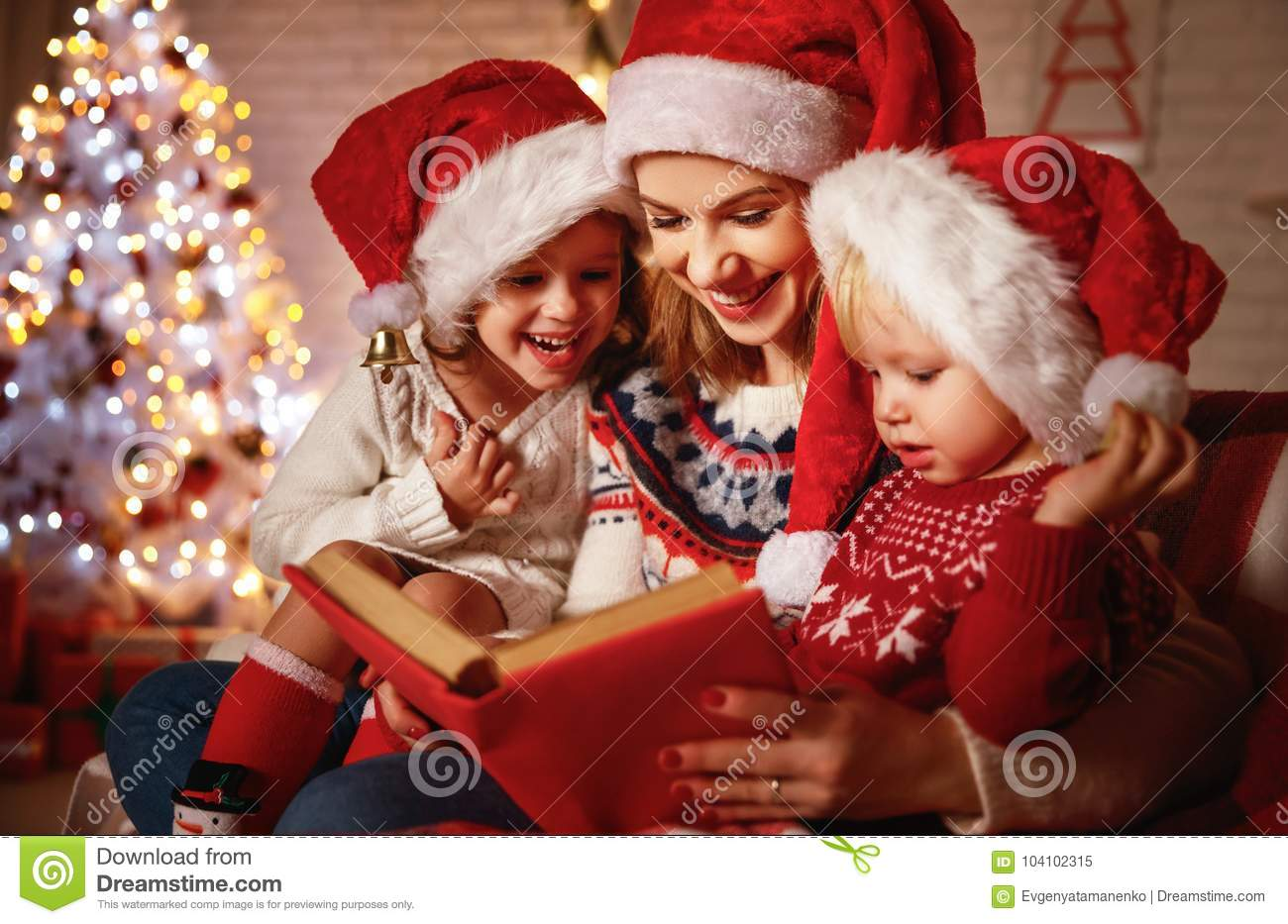 Family mother and children read a book at christmas near firep