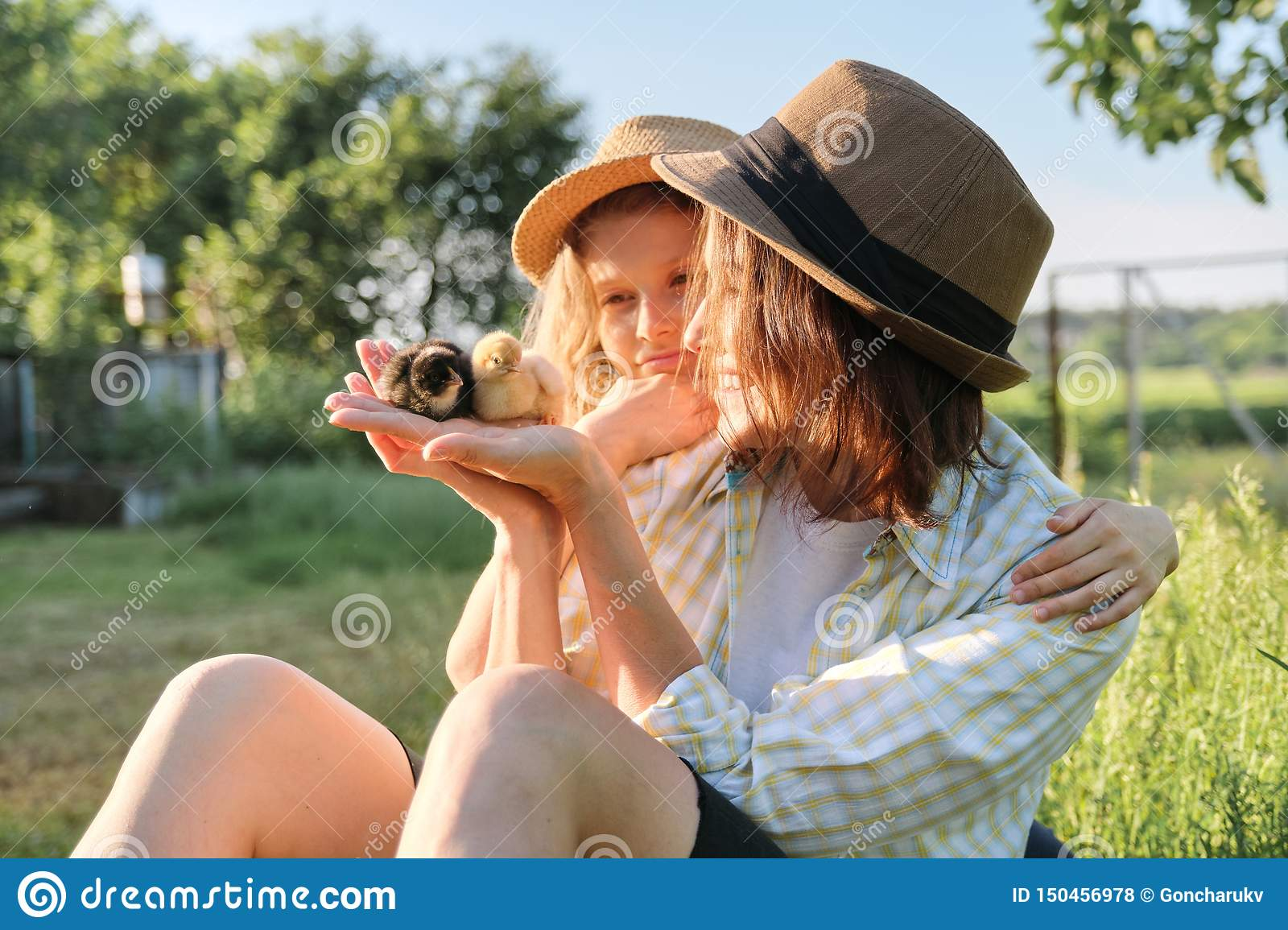 Happy family mother with daughter in nature, woman holding small newborn baby chicks in hands, farm, country rustic style