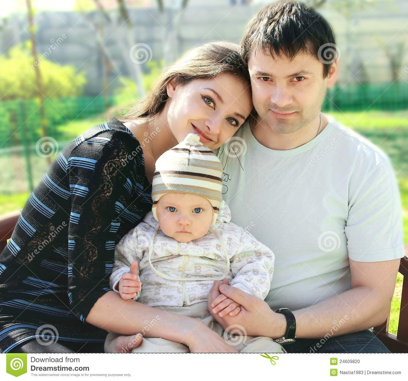 Happy family. Mother, father and baby in funny hat sitting on bench ...