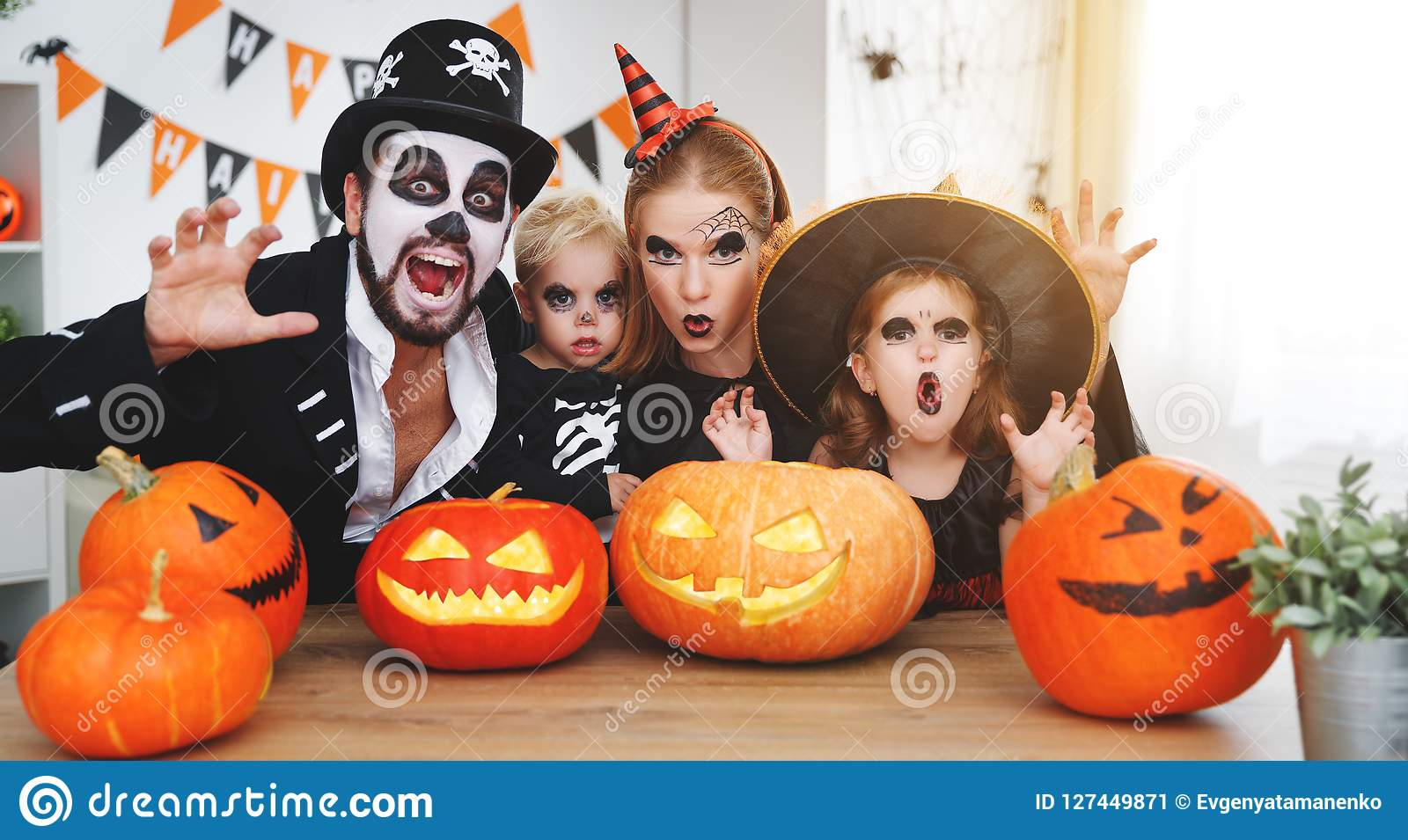 Happy family mother father and children in costumes and makeup o