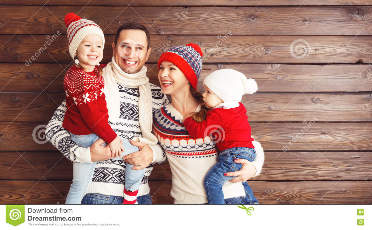 happy family mother, father and children in winter hats on wooden background