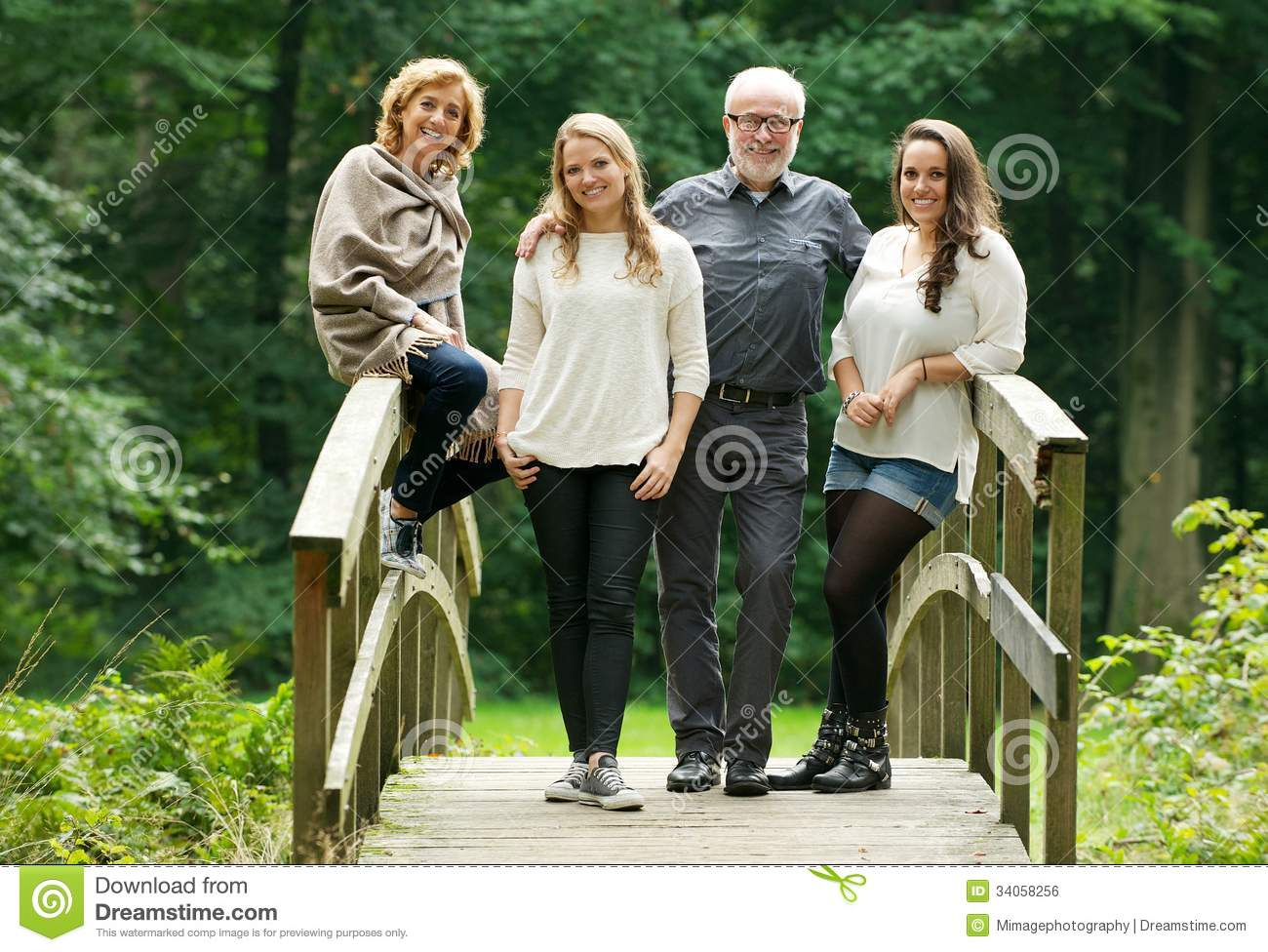 Happy family with mother father and daughters standing on bridge in the forest