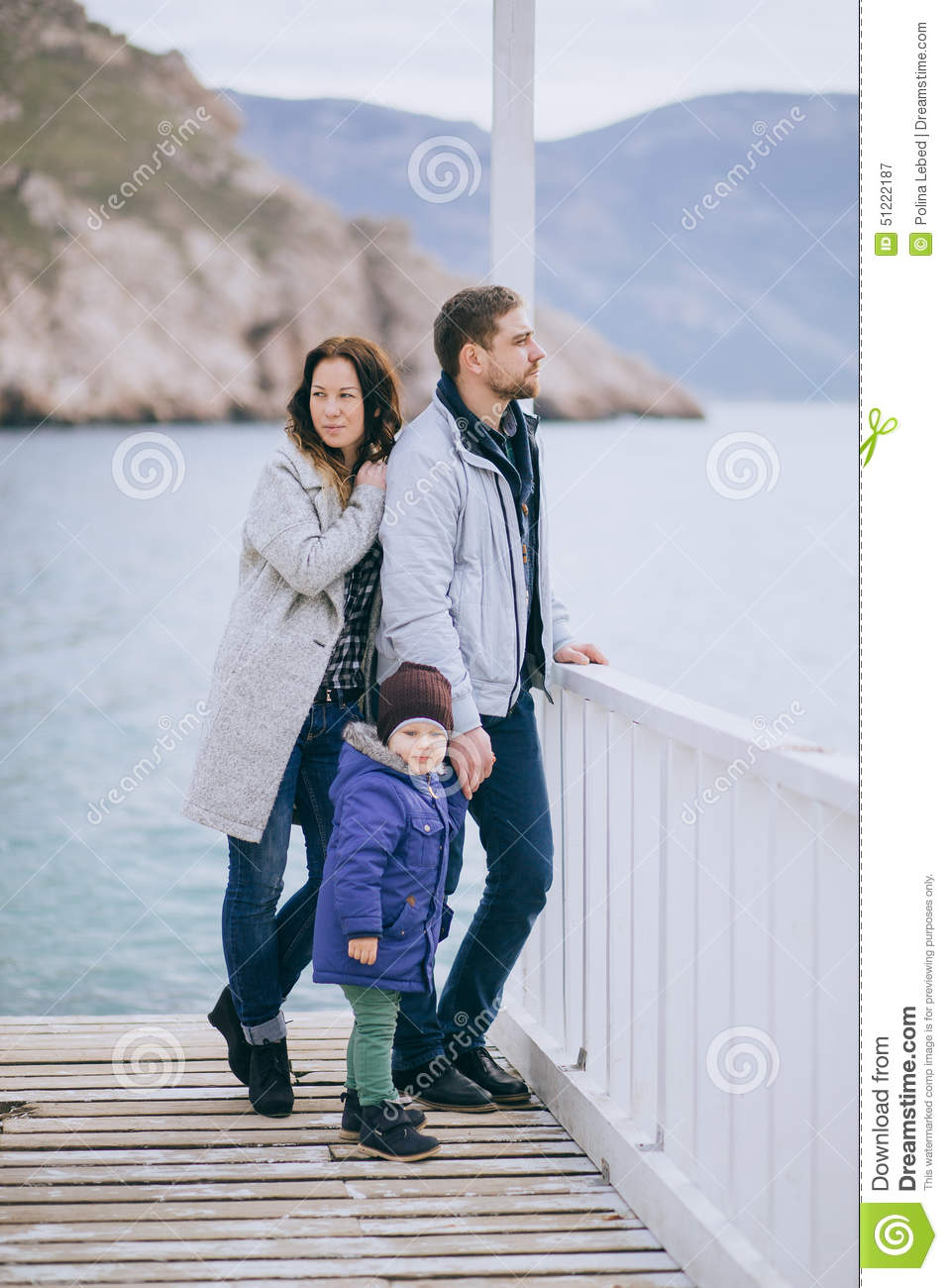 Happy family -mother, father and little son- walking in harbour