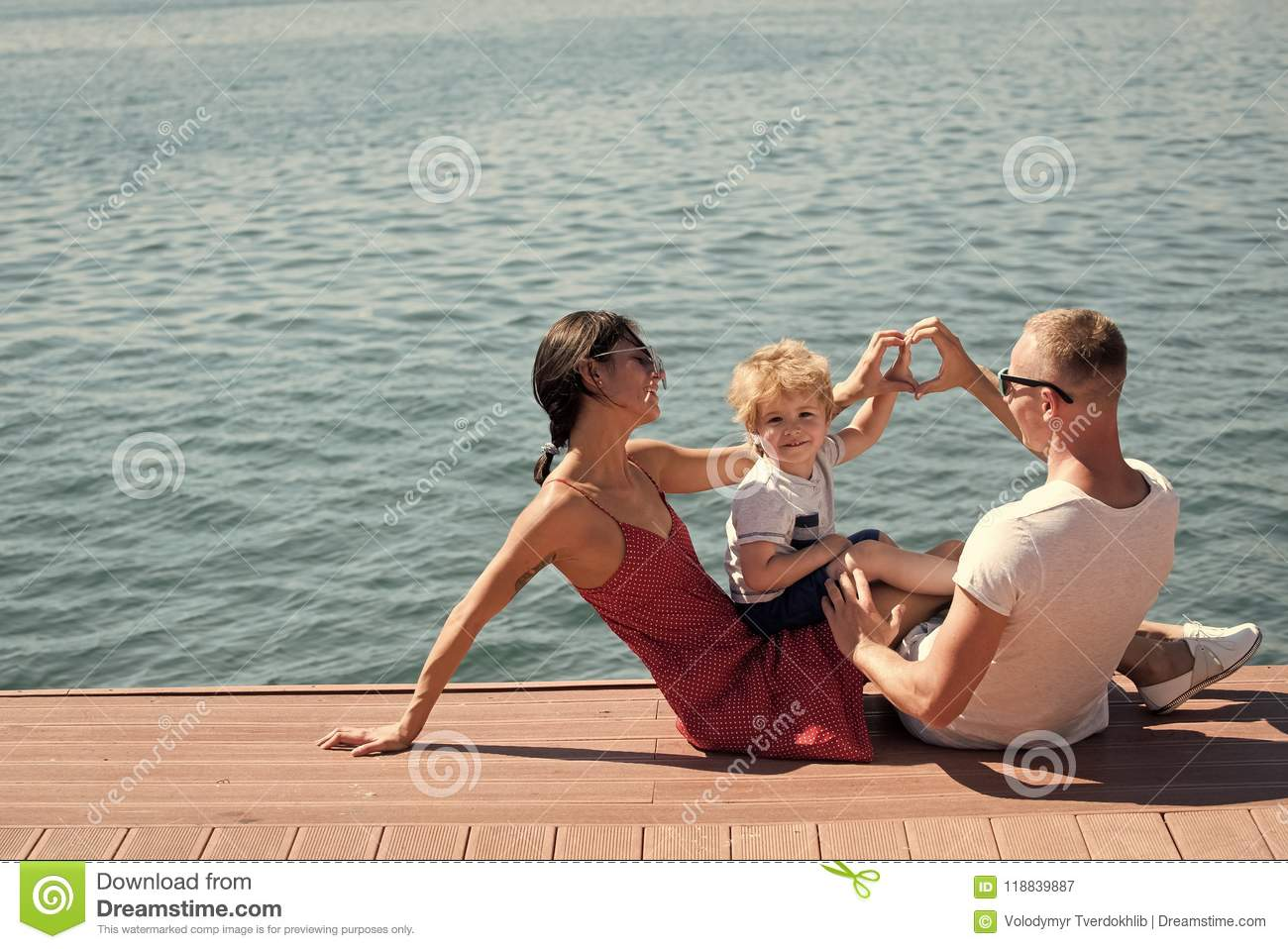 Happy family. Mother and father making heart or love gesture with hands near their child. Happy family spend time